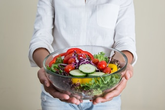 Girl showing her salad with cherry tomatoes and cucumbers