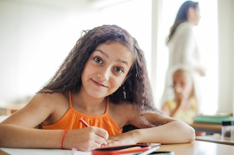 Girl sitting at desk holding pencil