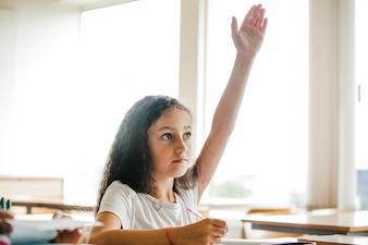 手を上げる学校のテーブルに座っている女の子