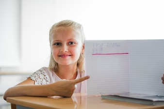 Girl sitting at school table with notebook