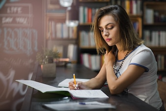 Girl sitting at table with notebooks writing