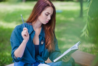 Girl sitting in park holding book reading