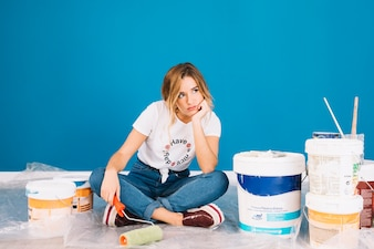 Girl sitting next to paint materials