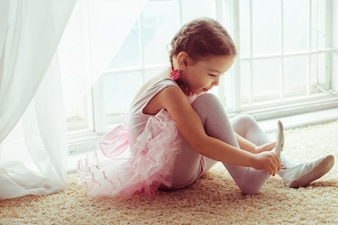 Girl sitting on floor putting on shoes