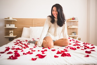 Girl sitting on knees on a bed with petals