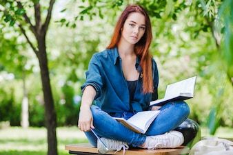 Girl sitting on table holding book