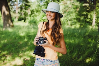 Girl smiling with a camera in hands and a hat