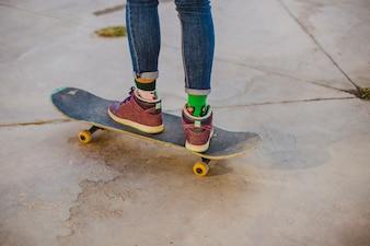 Girl standing on skateboard outside
