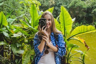 Girl taking photo in jungle front view