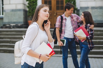 Girl talking phone near college
