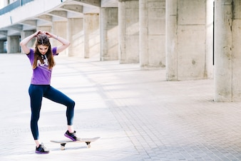 Girl touches her hair while holding her skateboard with one foot