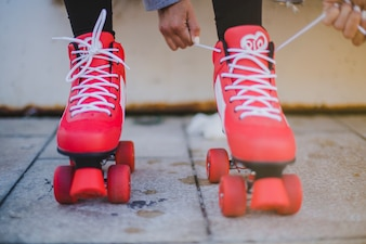 Girl tying red rollers with white laces