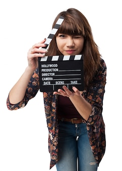 Girl winking and showing a clapperboard