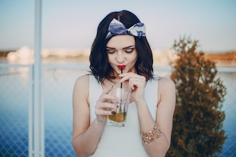Girl with a bow in her hair and white dress drinking from a straw
