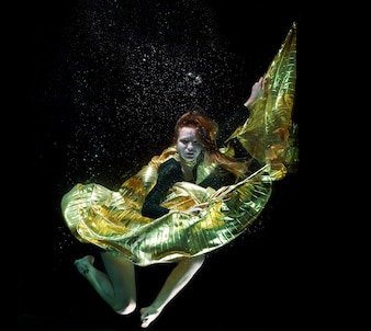 Girl with a golden cape under the water