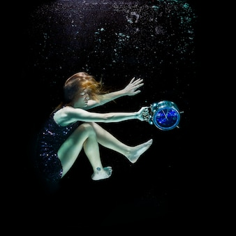 Girl with an alarm clock under the water
