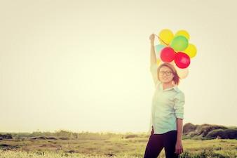 Girl with balloons aloft
