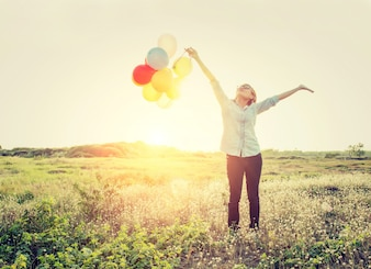 Girl with balloons and arms outstretched