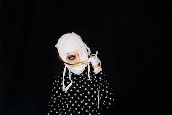 Girl with bandaged face on black background