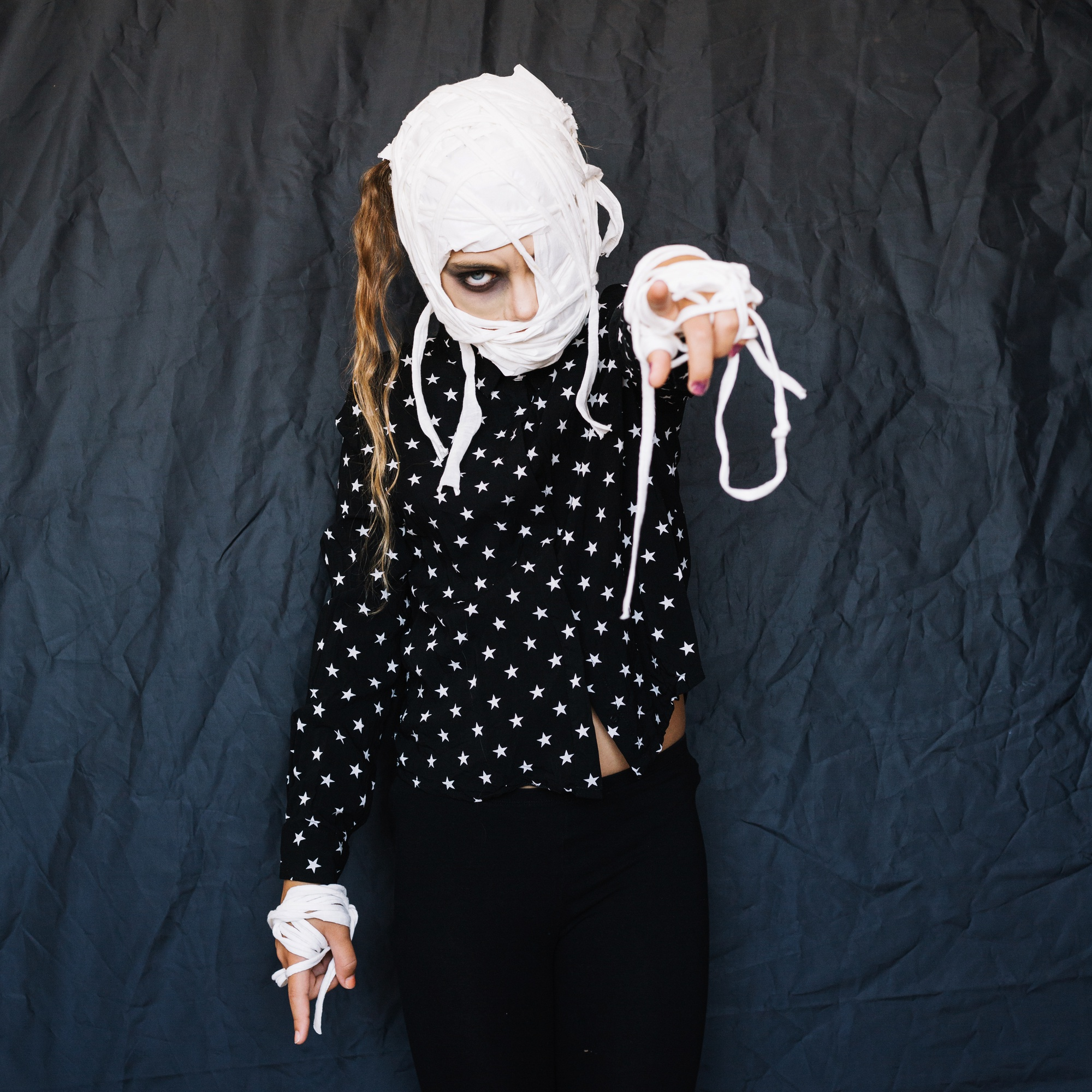 Girl with bandaged face pointing finger