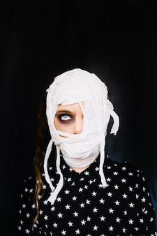 Girl with bandaged face rolling eye