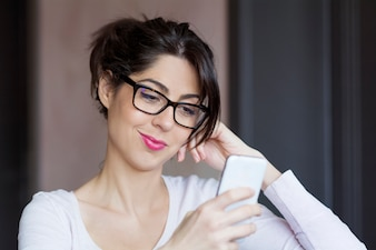 Girl with black glasses checking her smartphone