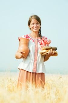 ライ麦のフィールドでパンを持つ少女