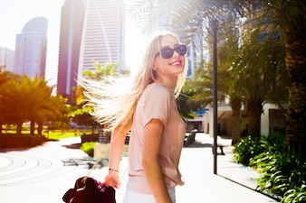 Girl with burgundi back shakes her hair standing on the street in Dubai