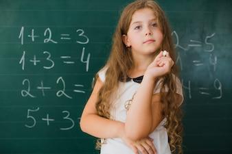 数学のクラスでチョークを持つ少女