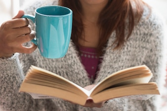 Girl with cup and open book