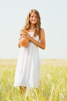 穀物畑でジャグを持つ少女