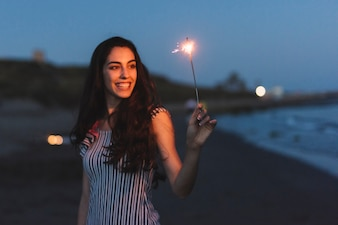 Girl with sparkler at the beach