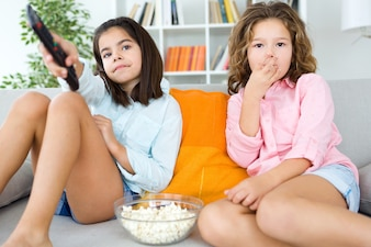 Girls eating popcorn and using remote