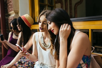 Girls on a terrace watching her phones