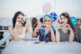 Girls sitting at a table smiling and making hearts with hands