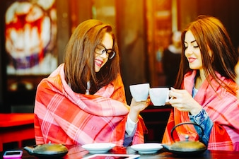 Girls toasting with cups of coffee covered with a blanket
