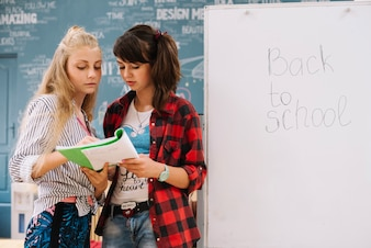 Girls with textbook at whiteboard