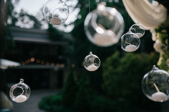 Glass balls with candles hang from wedding altar