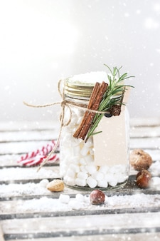 Glass jar with marshmallows and cinnamon tied with a rope