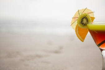 Glass of cocktail drink garnished with kiwi, lime and cocktail umbrella
