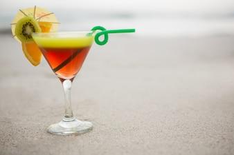 Glass of cocktail drink kept on sand