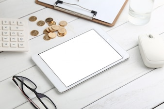 Glasses, calculator,coins and tablet on white neat desk