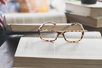 Glasses on opening book in library or cafe.
