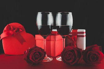 Glasses with red wine with two gifst and threeroses