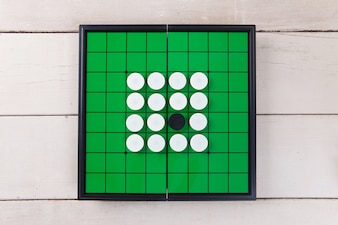 Go game on green board view from above on wood table.