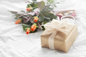 Golden gift package with a bouquet of flowers and chocolates