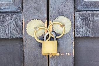 木製のドアに金色の南京錠と黄金のリング