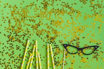 Golden sticks with golden confetti and glasses