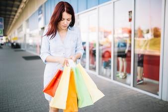 Good-looking woman looking at paper bags