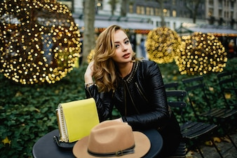 Gorgeous blonde woman sits at black round table before green bushes outside
